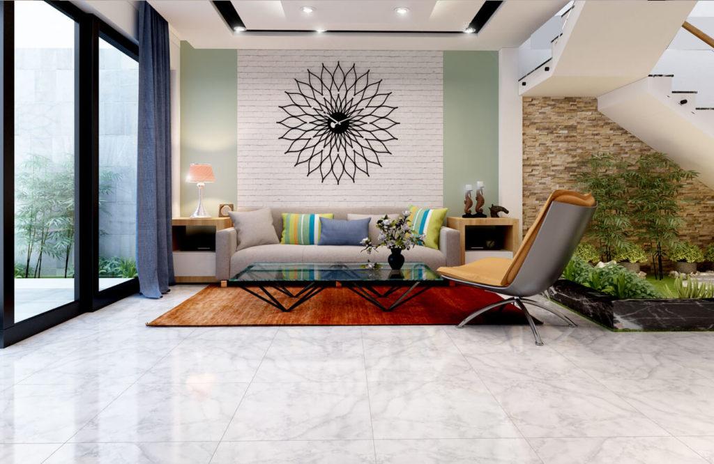 Phía sau sofa là một mãng tường trang trí đơn giản, với điểm nhấn là một chiếc đồng hồ độc đáo.